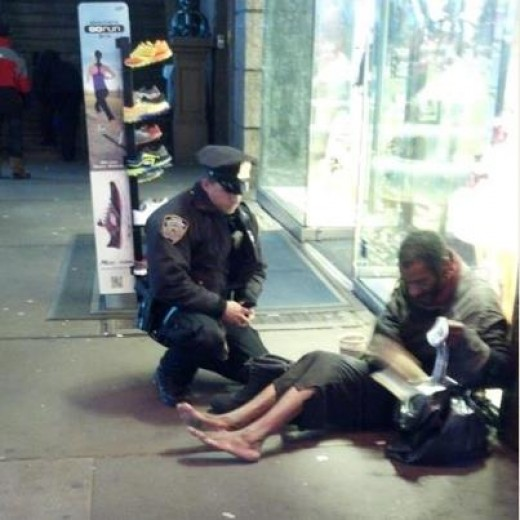 Image courtesy of Jennifer Foster (via NYPD facebook). The image depicts a New York City police officer giving a homeless man a pair of shoes.