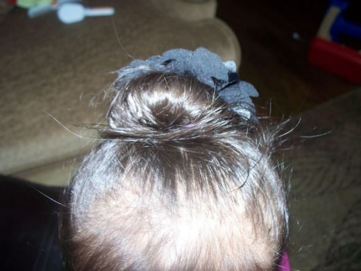 Place a giant bow or flower under the bun to finish off the hairstyle.