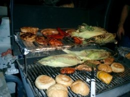 A complete meal, including corn on the cob,  on the BBQ grill