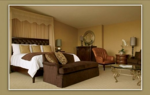 Bedroom has cream and brown color palettes with teak accents