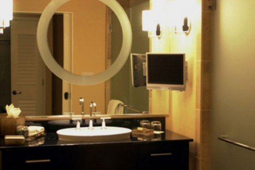 """Bathrooms are equiped with flat-screen 15"""" plasma televisions(wall mounted telephone not shown)."""