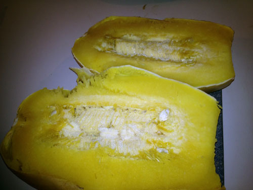 Once the squash is soft, remove from the oven and cut it in half. You will see a small rectangle of seeds and white fibers in the middle of each half.