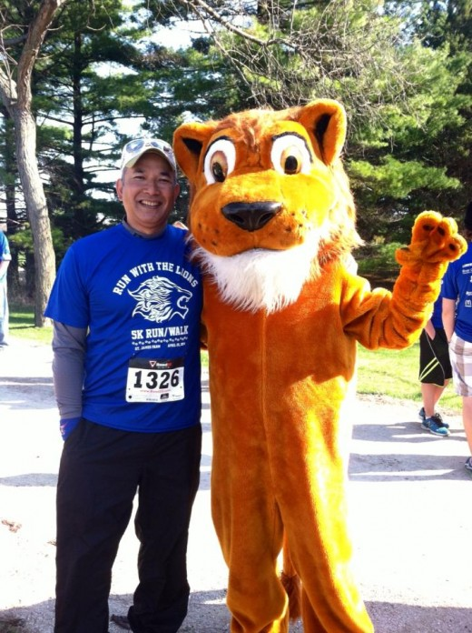 Runner posing with the Longwood Lion at our 1st 5K.