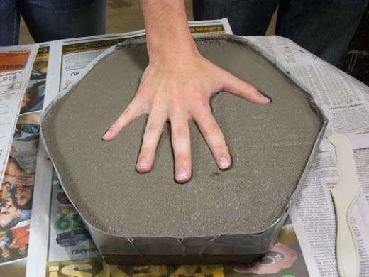 Step 7. Once your topper is smooth and even you can begin to decorate. Press your hand evenly into the wet mortar; you may have to use your other hand to help press down each finger to get a good imprint. Wash your hand of any residue before adding y