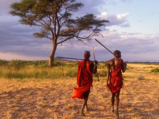 Two Masai Morans Walking with Spears at Sunset, Amboseli National Park, Kenya
