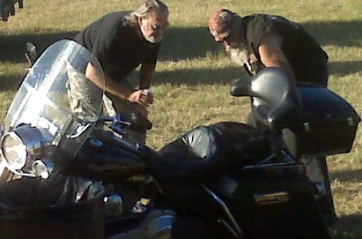A couple of bikers comparing notes on new paint job on bike.