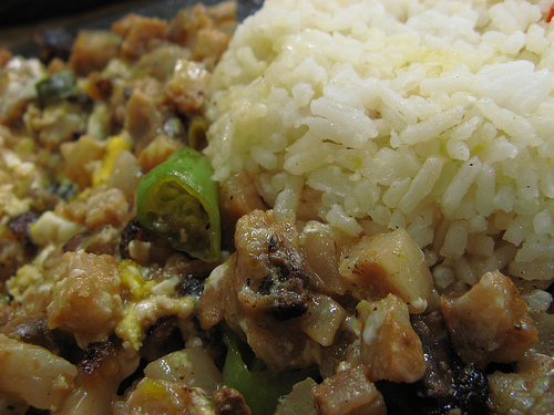 Spicy pork sisig with a whole egg cooked on top while sizzling hot, served with steamed rice (photo courtesy by sepia eye from Flickr).