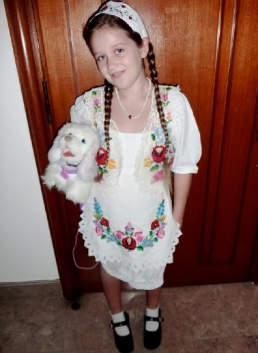 Emilia  is ready to go to her school's United Nations Day in Kalocsai costume in Singapore .