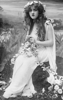 A black and white photo of Mignon Nevada as Ophelia, with a flower crown on her head and flower chain in her lap