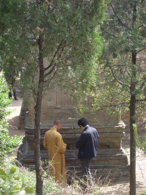 A Shaolin monk showing someone one of the dead monk's tombs.