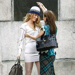 Blake Lively gets a little help with her Coach hat from costar Leighton Meester.