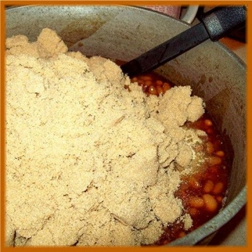 Once the beans are hot, lower the heat and add a whole 2 pound bag of brown sugar.