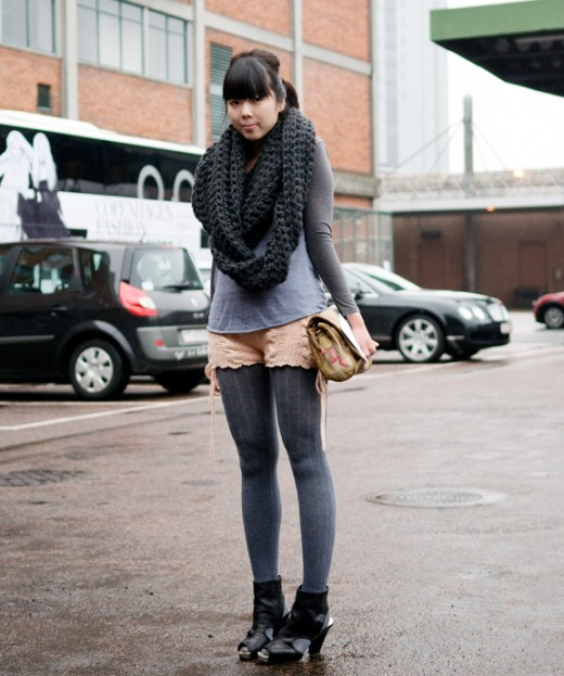 Beautiful Japanese woman wearing a street fashion attire rather well with black stockings that raise up her thighs to just beneath her gray skirt.