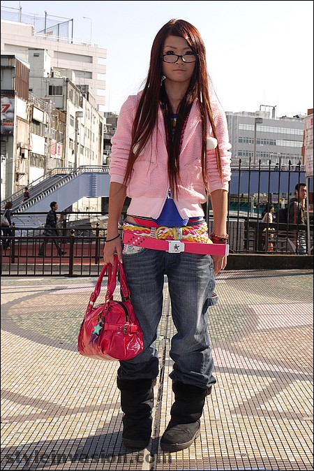Cute Asian woman wearing jeans, pink belts and light pink short cut shirt with a dark pink handbag.