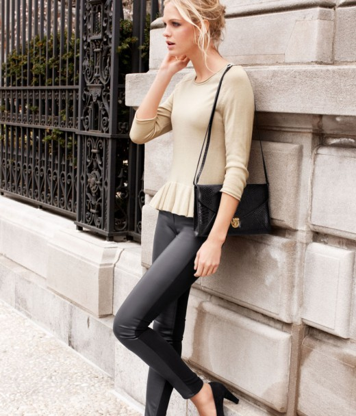 This hot blonde wears street fashion well with a beige bright sweater and skin tight jeans and a black handbag.