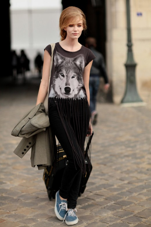 Woman walking the streets with a t shirt that has print of wolf and black pants.