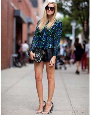 Her street fashion allows her to exhibit beautiful long legs with shades, blue printed jacket and black handbag.