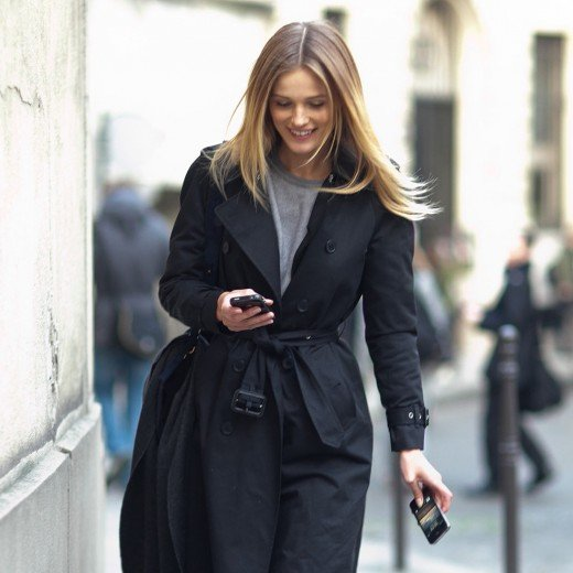 Exquisite street fashion with a black trench as she tots her cell phone along her down the street.