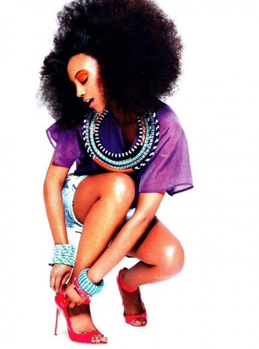Attractive woman wearing blow out Afro with Indian necklace and shorts stilettos street style showing her smooth legs.