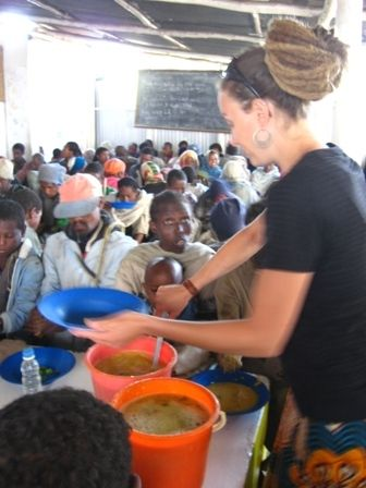 Volunteers work in a local feeding center where meals are provided