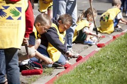 Wearing adult-sized Mormon Helping Hands yellow vests, a cadre of children gives service while rolling red paint onto a curb in Santa Clarita, Calif.