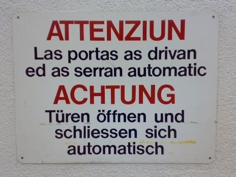 "Bilingual warning notice in Zernez (Gr, CH): ""Doors open and close automatically""."