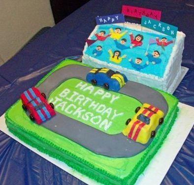 "All pieces carved from two oblong cakes.  Cars are cake covered in fondant.  Royal icing ""fans""."
