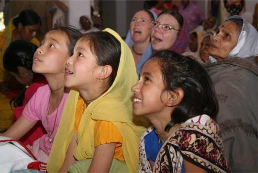 devotees gazing lovingly at Sri Nityananda in the temple