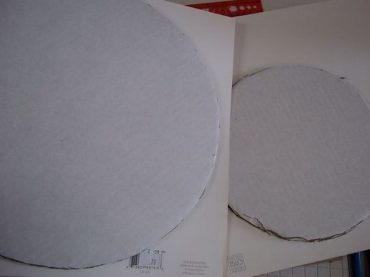 """First I sprayed the top of each circle and stuck them to the back side of the paper I'm using as a cover. It's a good idea to """"dry fit"""" these first, so you know the paper is big enough."""