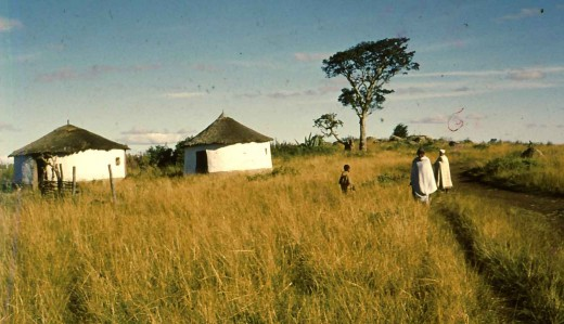A homestead on the road. The people are wearing white blankets which indicate that they are Christians