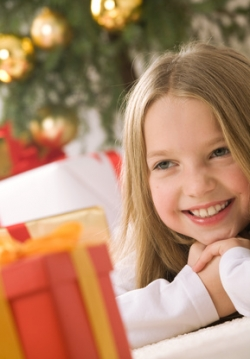 girl with gifts sitting by the Christmas tree