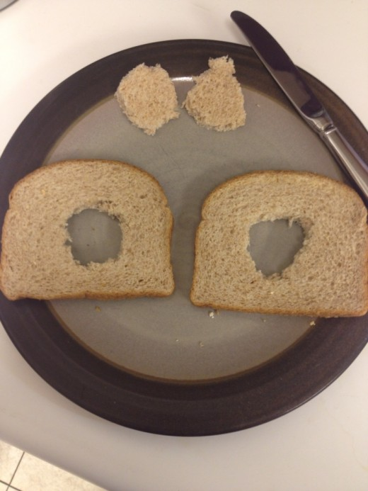 Cut holes from center of bread.