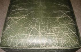 High traffic area of leather sofa cushion with scrapes, scratches and color loss, visible years of wear and tear