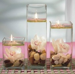 Floating candles with clear vase with rocks and a single orchid