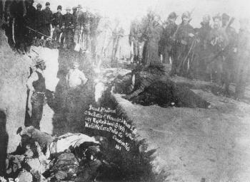 Civilian grave diggers bury the Lakota dead in  a mass grave.