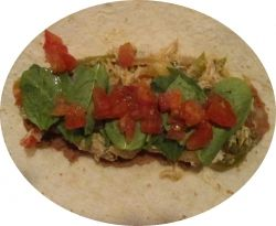 A soft flour tortilla shell with refried beans, shredded chicken in salsa, spinach and diced tomatoes.