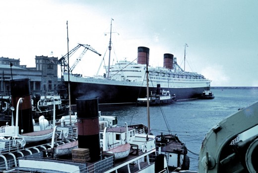 RMS Queen Elizabeth, with tugboats alongside, and in the foreground.  In Cherborg, France,  1966.   Original photo by Roland Godefroy