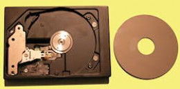 Inside a computer's disc drive. The disc itself has been removed and is on the right. It's normally mounted on the motor spindle - the silver circle in the centre of the circular depression in the drive.