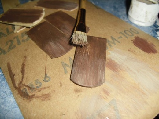 Drybrush a lighter color with your stiff bristled brush. Use an almost dry brush. Wipe most of the paint off on newsprint (or on the back of your sandpaper!) before you attempt to paint the shingle. Here it is very important to paint in a downward