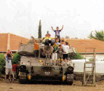 Celebrating Independence Day on the Golan Heights.  A group of young boys on top of a tank after a celebration involving an army display.