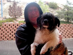 A smiling Malcolm just back from a walk in the rain with a wet not so happy Scraggy