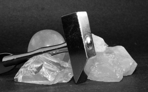Quartz Crystal and Rock Hammer Against A Black Background
