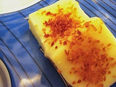 "Maja Blanca is a mixture of coconut milk, cornstarch, sugar , corn kernel, roasted peanuts and topped with "" latik"""