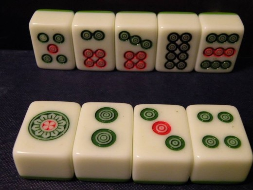 Circles Suit: Four tiles each of numbers 1-9. These pieces are used to make sets and runs of three.