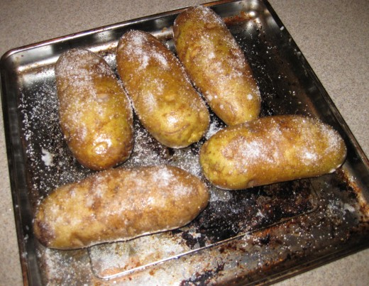Cover the potatoes completely with a coat of oil (easy to just rub it in by hand). Then salt HEAVILY all over the potato.