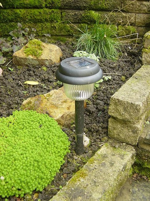 The most common easy-install method for a solar-powered light involves driving the spike at the bottom on the light into soil.