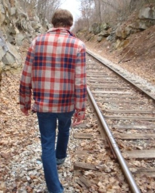 Flannel shirt dude walking the lonely tracks.