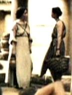 Two women in a background scene. The woman on the left has an outfit similar to Leonidas' mother's drapery dress, minus the drapes.
