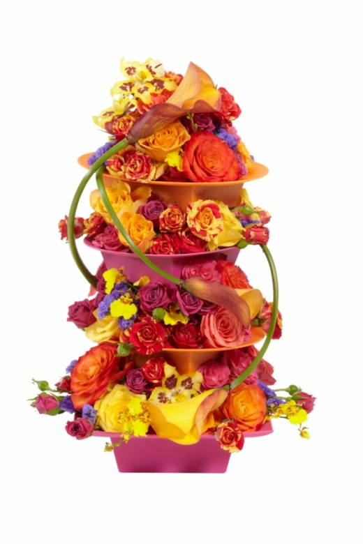 This amazing extravanganza is made from a number of containers filed on top of each other, in this case the containers come from smithers oasis and the layers are linked with calla lilies held in place by iglu dots.