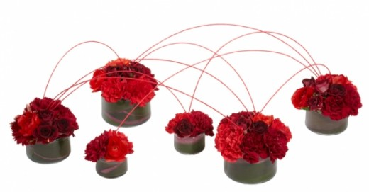 Red roses are never out of fashion, but recently the trend has been to combine colors and textures of red. This is done brilliantly in this arrangement of low bowls. Low cylinder vases contain Oasis floral foam wrapped in red Ti leaves. The foam is f